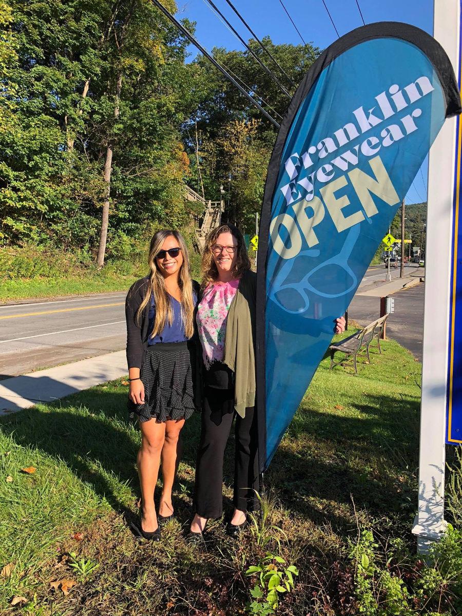 Photo of Hanna VanDeusen and Dr. Helen Luu Garner with Franklin Eyewer sign